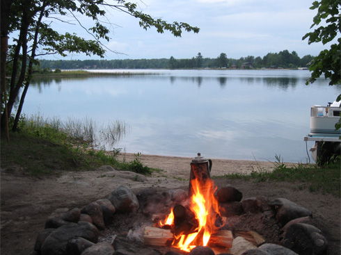 campfire with coffee pot by the lake